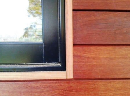 Cumaru rainscreen installation with wood trim at window