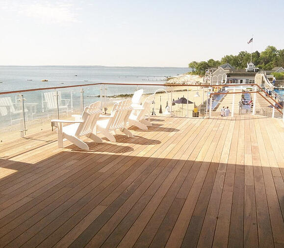 Ipe hardwood deck on the oceanfront  beach with white deck chairs