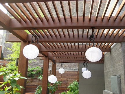 Ipe hardwood decking with pergola arbor in a city patio area, with hanging white globe lights