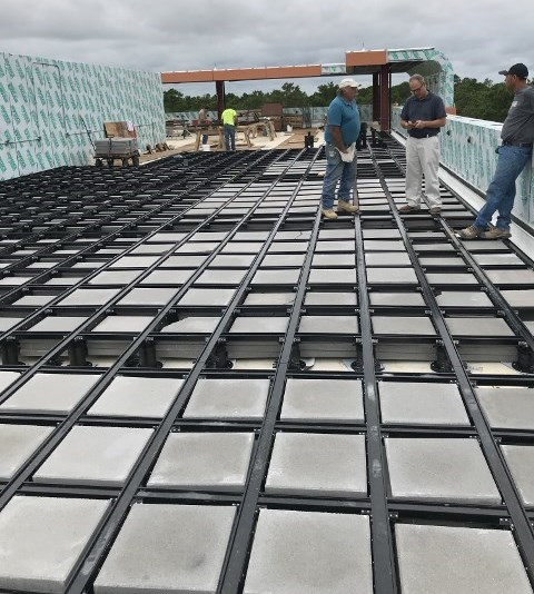 Rooftop deck frame with concrete ballast is expansive
