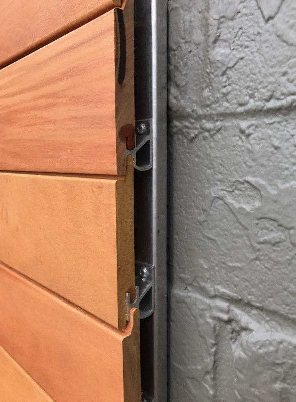 Garapa hardwood siding fastened to Climate-Shield Rain Screen attachment channel over masonry