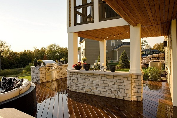 A photo of an Ipe wood deck freshly sealed with seating and a stone outdoor kitchen plus a 2nd level wood deck balcony above it.
