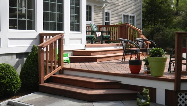 A bi-level hardwood porch with cumaru decking and ipe railing system, with planters and patio furniture.